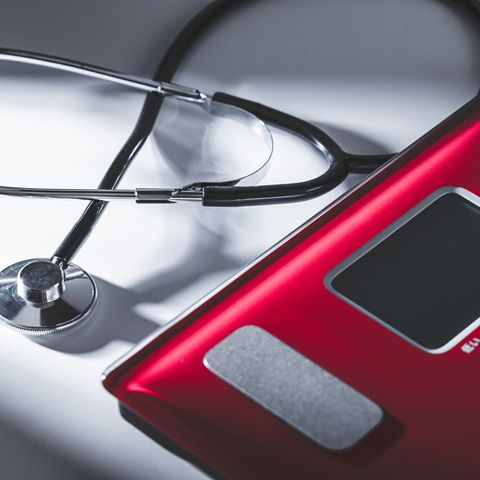 stethoscope and weight scale  on white background