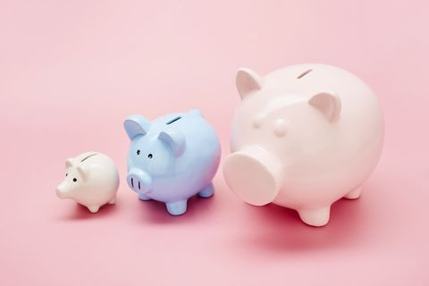 still life of differently sized white, blue and pink piggy banks in ascending size order on pink background