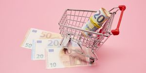 Still life of shopping cart and Euro notes on pink background
