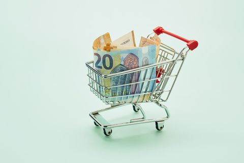 still life of shopping cart and euro notes on turquoise background