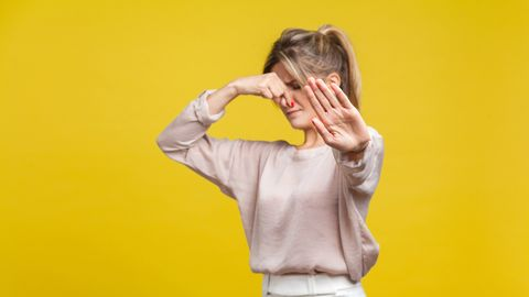 stinky smell portrait of young dissatisfied woman with fair hair in casual beige blouse, isolated on yellow background