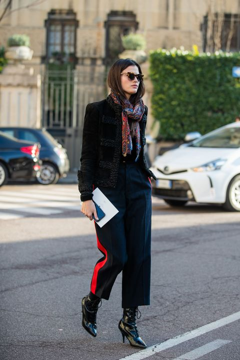 milan, italy   january 12 a guest is seen wearing black jacket, navy pants with red strip, scarf with print outside ferragamo during milan fashion week fallwinter 20202021 on january 12, 2020 in milan, italy photo by christian vieriggetty images