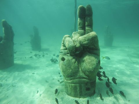 stone hand is set underwater to attract fish while snorkeling off coast, mexico