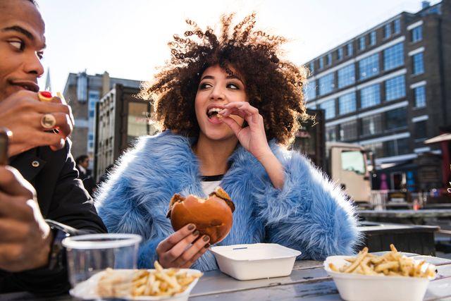 jonge vrouw die een burger eet