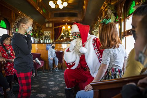 a masked santa is on an old fashioned train car kneeling in front of a little girl who is smiling behind her own mask there are other kids looking on