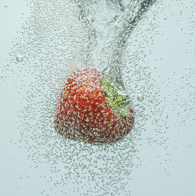 strawberry falling in fizzy water