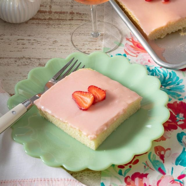 strawberry rose sheet cake on two green plates in front with cake and rose in back