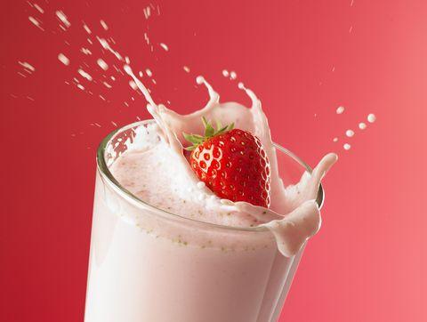 strawberry splashing into smoothie
