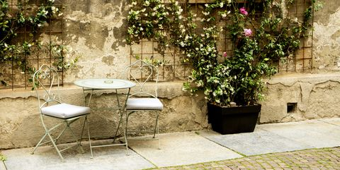 a street scene with iron chairs and table, old wall an potted plants alba, italy