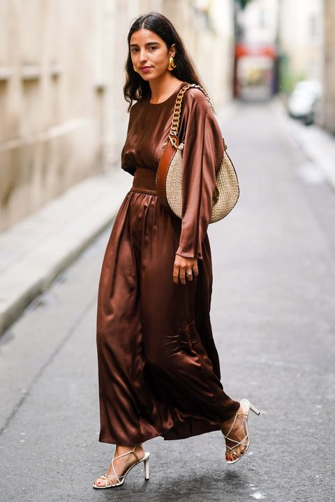 paris, france   september 29 bettina looney wears a brown lustrous shiny dress, a loewe large bag, heels shoes, earrings, outside thom browne, during paris fashion week   womenswear spring summer 2020, on september 29, 2019 in paris, france photo by edward berthelotgetty images