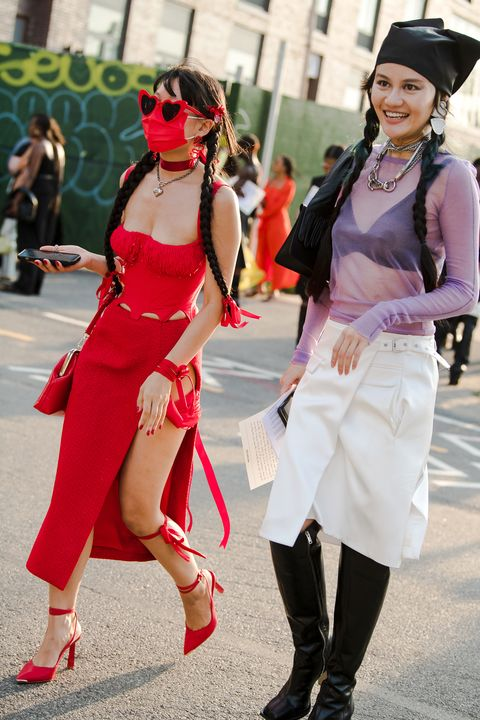 a red look and a visible bra are part of street style at new york fashion week