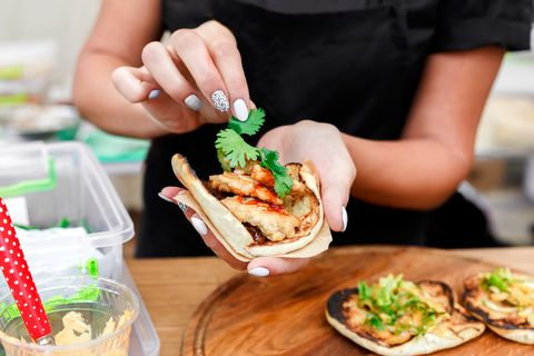 Street vendor hands making taco outdoors