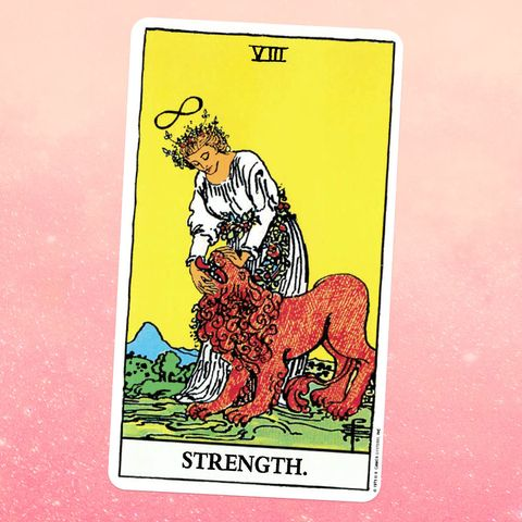the strength tarot card a woman in a white dress pets a lion