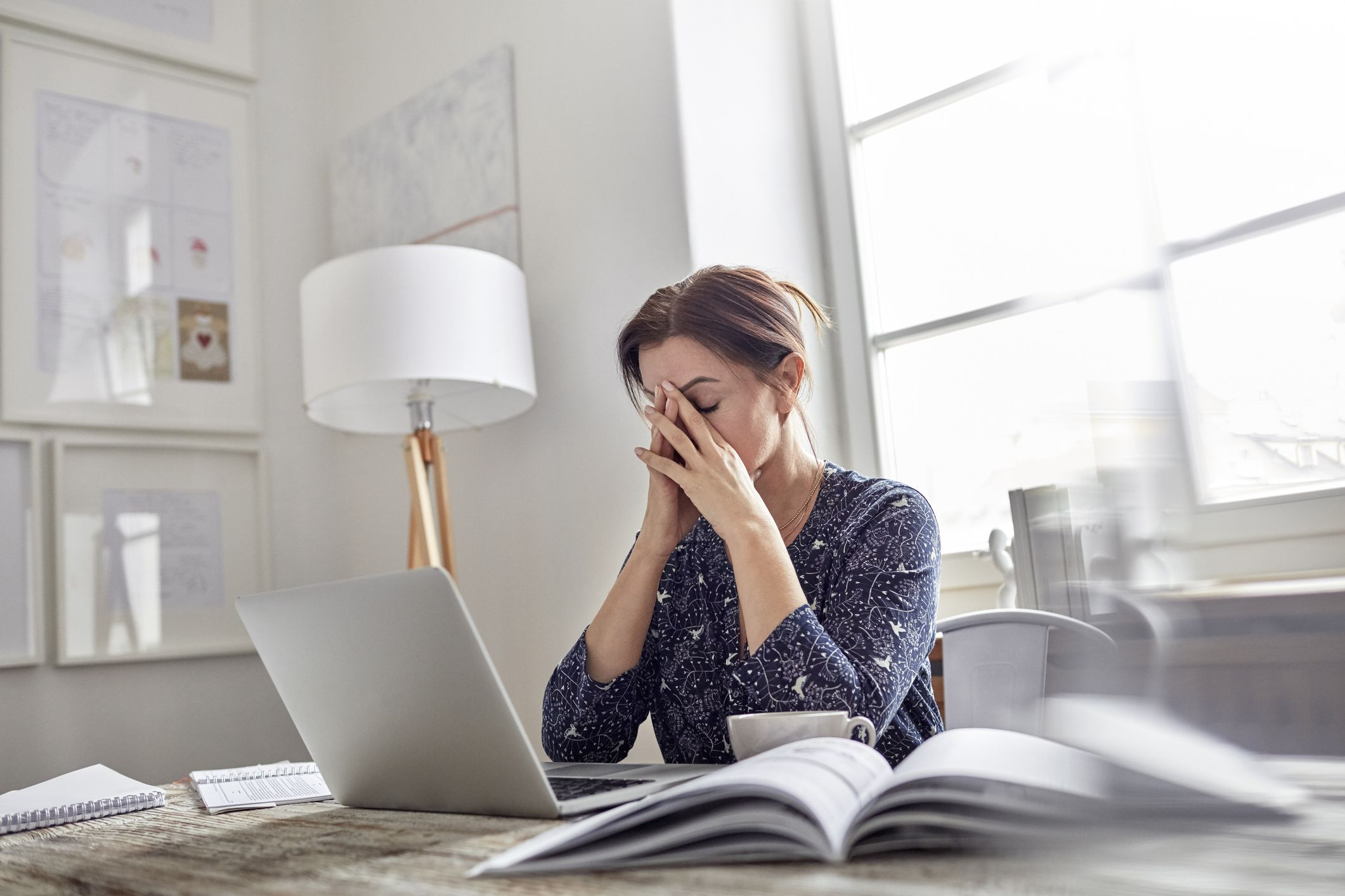 Stressed woman cradling face in hands while sitting behind computer.