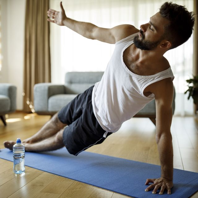strong athletic young man exercising at his home