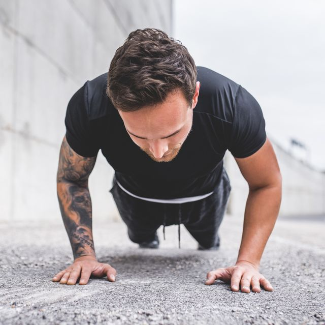 strong male athlete doing outdoor push ups