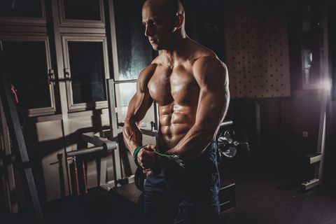 Strong Muscular Man Standing At The Gym