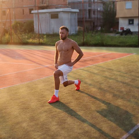 Strong sporty man stretching his legs before training. Standing in tennis playground on hot summer morning.