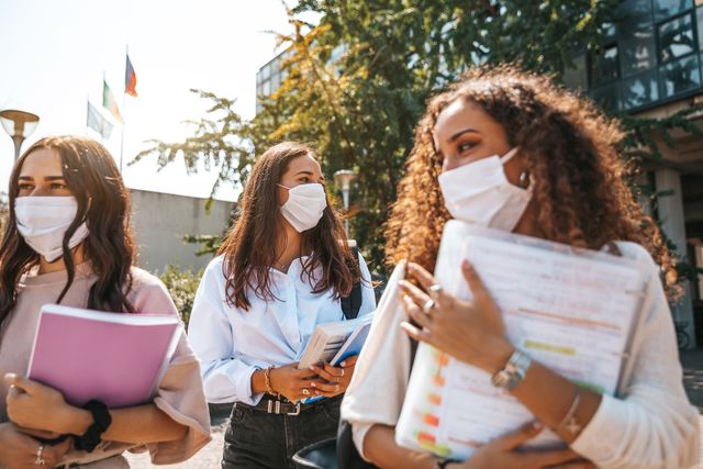 students wearing protective face masks walking out from school