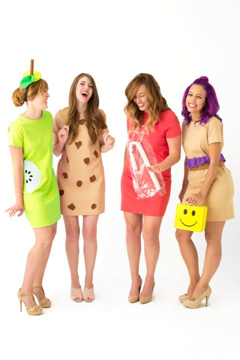 """four laughing women in short dresses dressed as """"lunch ladies,"""" one carrying a yellow smiley face lunch box"""