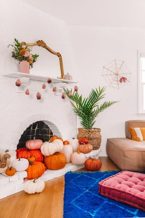 there is a small round fireplace with pumpkins coming out of it, a tassel garland hung from the shelf above it, with a gold mirror, pumpkins and flowers in a pink vase on the shelf  there is also a yarn spiderweb on wall beside the fireplace, and a blue rug in front of the fireplace, with a pink tufted cushion on it and a tan leather chair beside it