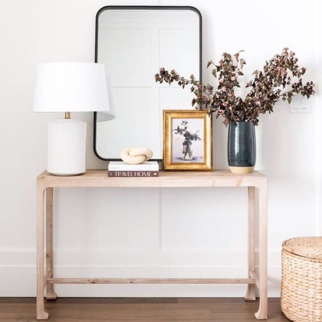 entryway table with mirror, vase, lamp, picture frame living room with couch and potted plant