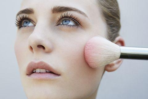 Studio shot of female model and pink blusher brush