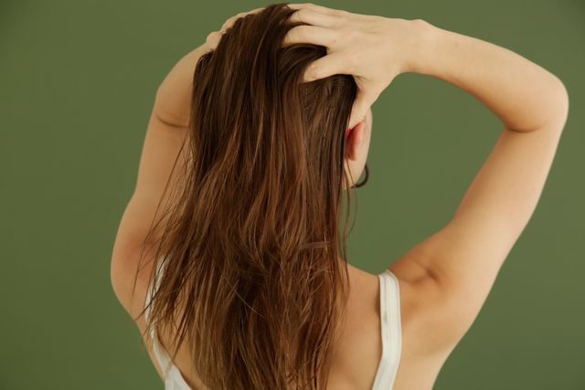 studio shot of woman applying hair oil with her fingers