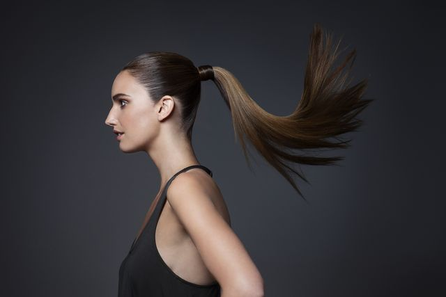 studio shot of young woman tossing hair