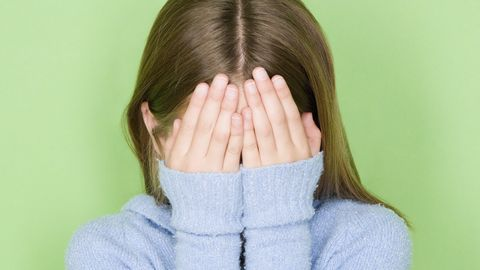 studio shot portrait of teenage girl covering face, head and shoulders