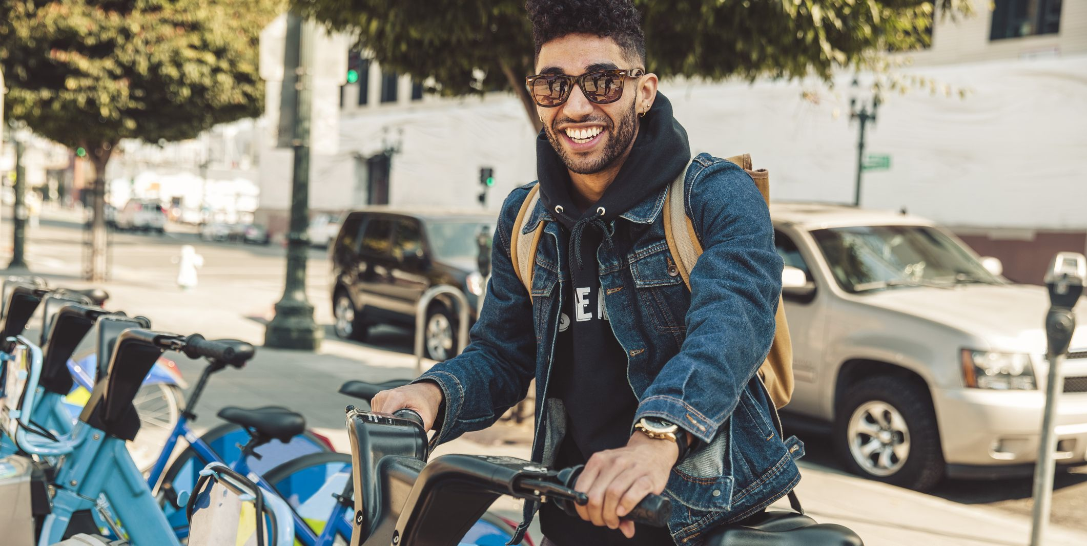 Stylish young man on the street with rental bike