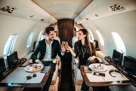 successful couple making a toast with champagne glasses while having canapes aboard a private airplane