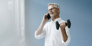Successful manager using smartphone and training with a dumbbell