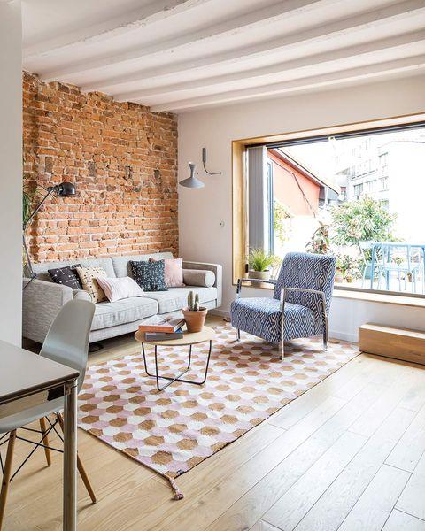 Salón con pared de ladrillo y gran ventanal