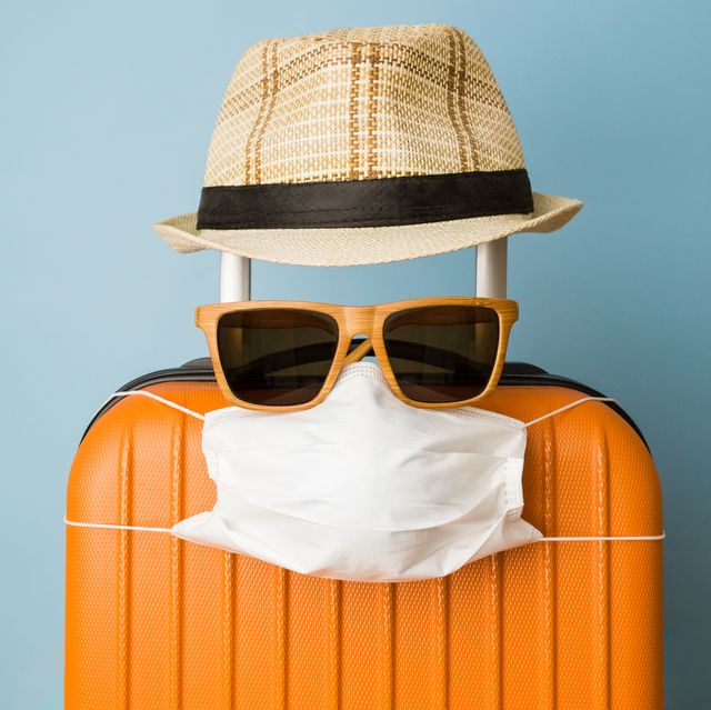 suitcase with hat, sunglasses and protective medical mask on pastel blue background minimal creative coronavirus covid 19 travel concept