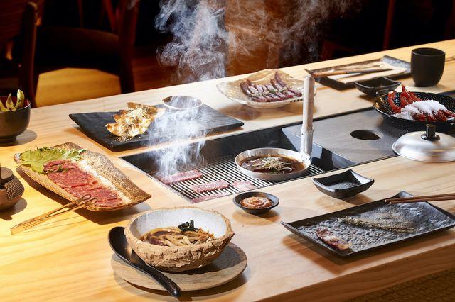 diversos platos sobre una mesa con parrilla de carbón en el restaurante pilar akaneya