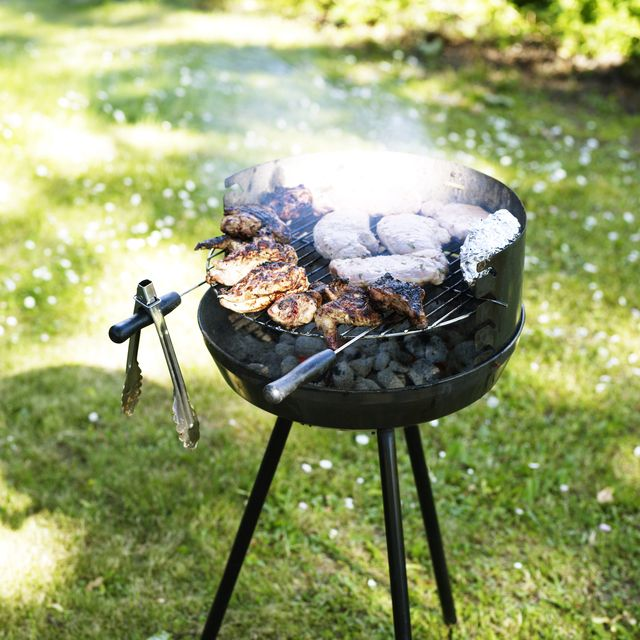 bbq on the lawn with meat roasting on the grill and tongs hanging from the side