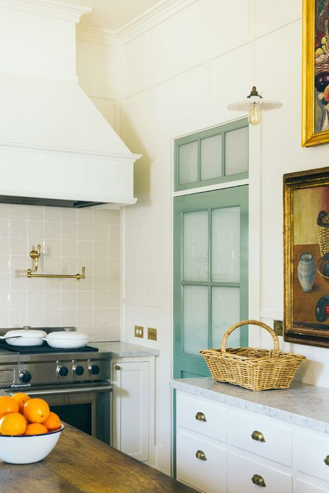 kitchen with mint green door and bowl of oranges