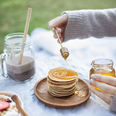 summer healthy vegetarian picnic in park womans hand pouring organic honey on delicious stack of pancakes fruits, cacao, honey pancakes and organic granola on linen tablecloth decorated with pillows and wicker basket