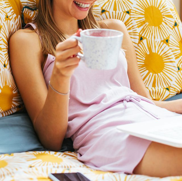 woman laying in bed with laptop and coffee mug in pajamas