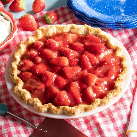 strawberry pie with blue plates in back
