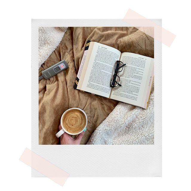 zarah using sunbeam heated throw blanket with coffee and a book