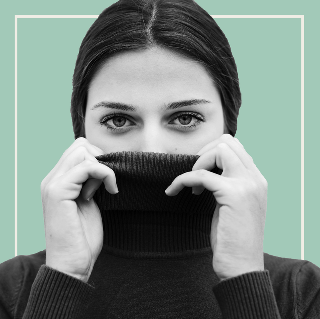 woman covering half of her face with a turtleneck