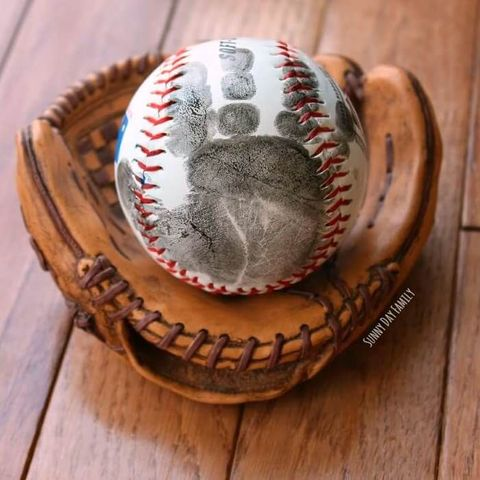 baseball with child's hand print on it inside baseball glove