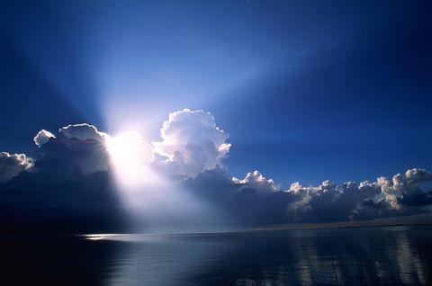 sun's rays breaking through cumulus clouds over ocean, florida, usa