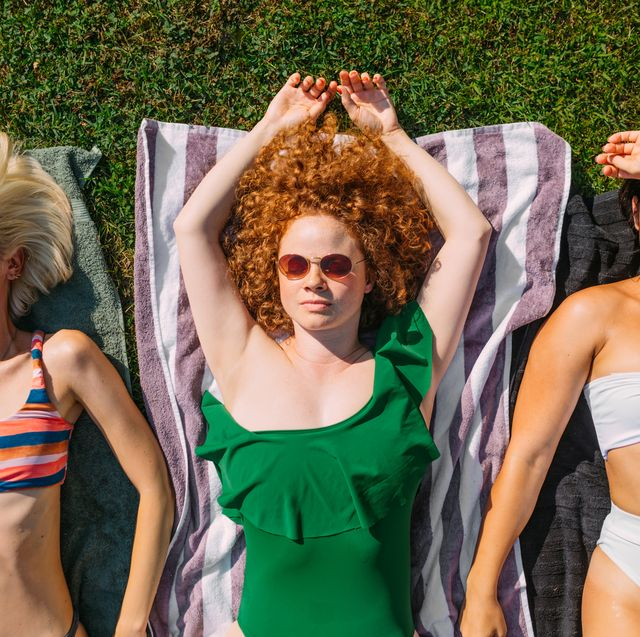 3 girls laying out in sun on beach towels
