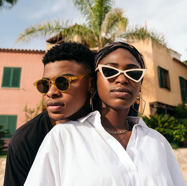 man and woman wearing sunglasses in front of palm trees