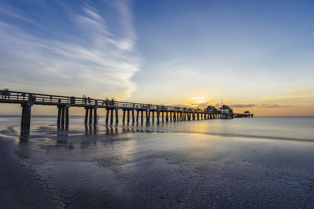 sunset over naples pier in florida from the beach