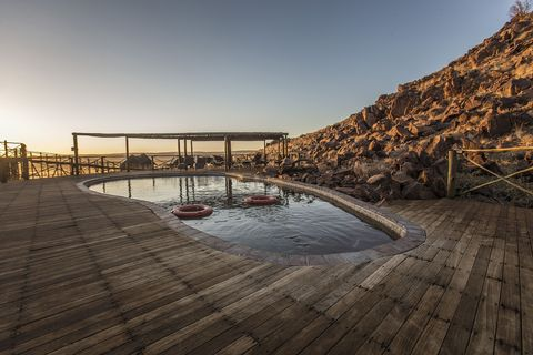 swimmingpool with wooden deck at sossus dune lodge in namibia