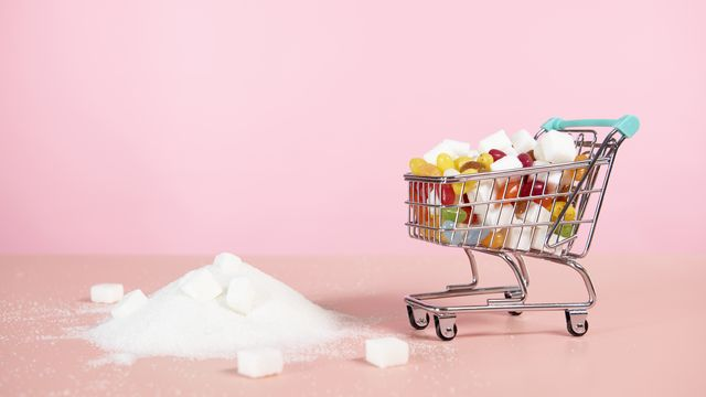 supermarket trolley with candy next to pile of sugar